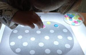alumna haciendo ficha de calabaza en caja de luz